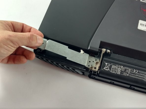 Lift away the metal housings from the laptop to uncover two additional screws on each side of the laptop.