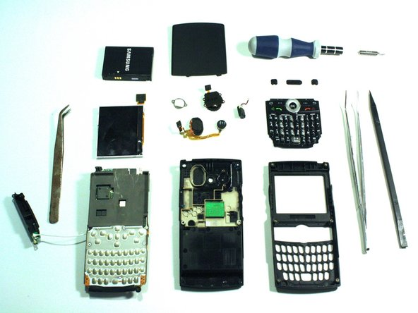 Image 1/1: From top to bottom, left to right: battery, back cover, screw handle, PH00 screw bit, small tweezers, camera screen, antenna cover, antenna and speaker, volume dial, speaker, power button, volume, button, back button, keypad cover, tweezers, spudger, logic board, back case, front case