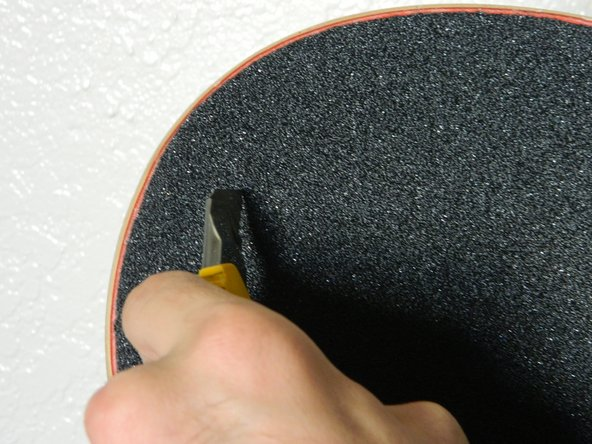 If air bubbles persist, gently use a utility knife to poke a small hole in the grip tape at the center of the bubble and press out the air.
