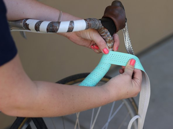 Continue to tightly wrap the bar tape around the bar as evenly as possible.