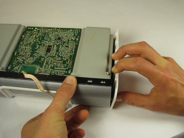 Image 2/2: Using both hands, pull the housing siding away from the device while simultaneously lifting the motherboard and speaker assembly straight up.