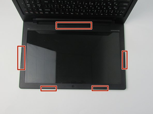 Carefully remove the laptop screen impact strips using the plastic spudger