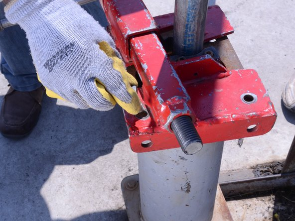 Secure the base clamp to the frame base using a bolt.