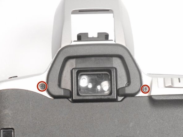 The only screws remaining that hold the top panel of the camera in place are located next to the view finder.