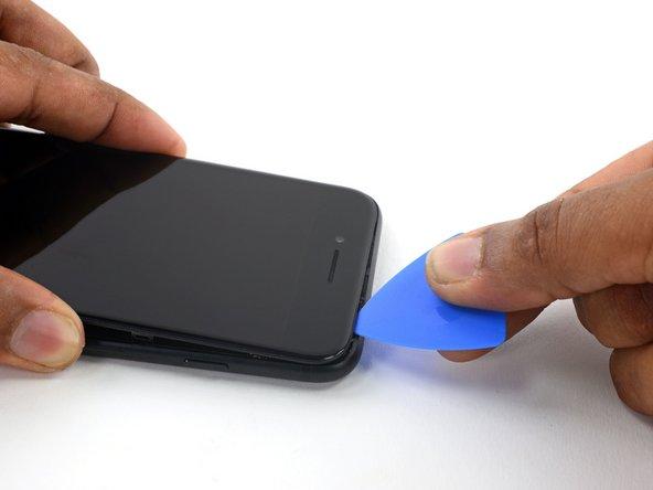 Fai scorrere uno strumento di apertura lungo il lato superiore della iPhone, tra il case posteriore e il pannello anteriore, per rompere la parte restante dell'adesivo che tiene in posizione lo schermo.