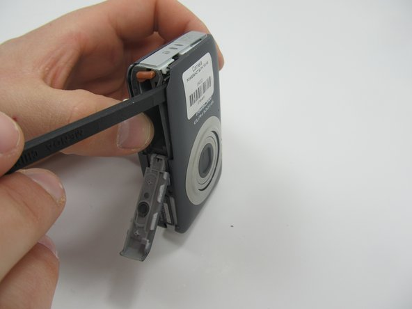 With the battery door still open, use a spudger to remove the cover from the front of the camera.