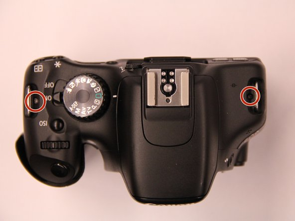 On the top cover, remove the two screws from under the metal tabs that are used to attach the camera straps.