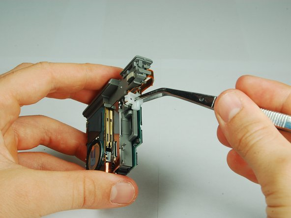 Use tweezers to remove the small white piece from the motherboard assembly.