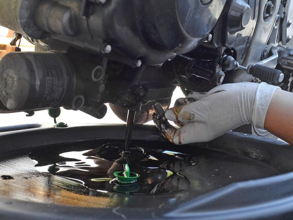 Finish removing the oil drain plug by hand and allow the oil to drain.