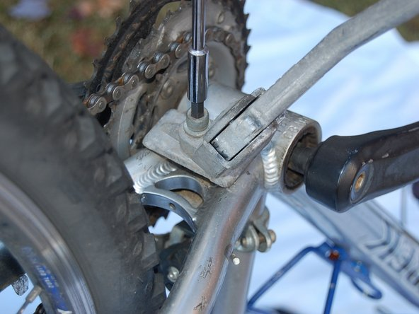 Using a socket screwdriver with a hex adapter, loosen the bolt that is holding the kickstand and bracket in place.