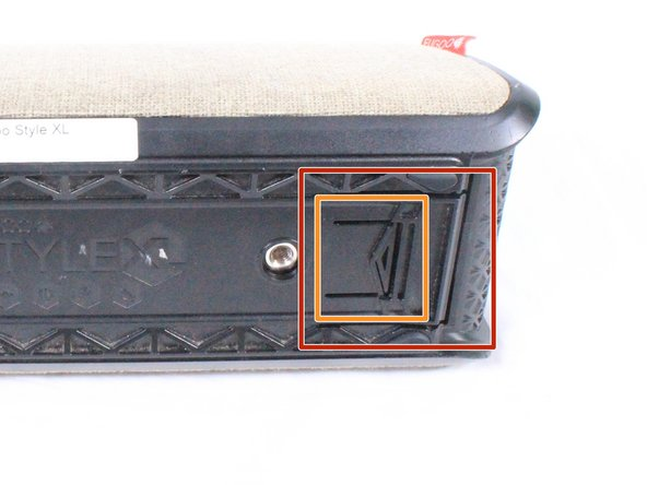Using your hand, gently lift the large plastic tab secured to the rubber holding (the holding is within the orange square). While lifting the tab, push the speaker out of the case.