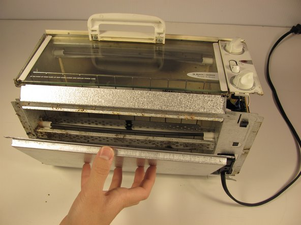 Remove the crumb tray (bottom metal panel) from the toaster unit.