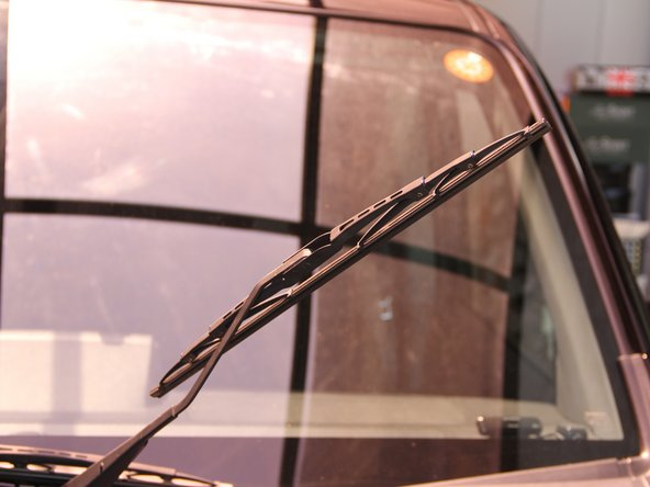 Return the windshield wiper blade back to its original orientation.