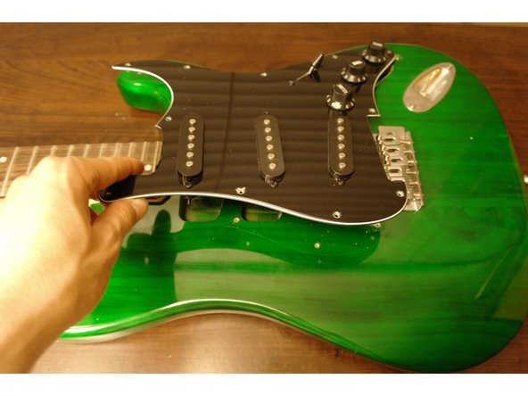 Carefully lift the panel of the guitar and turn it upside down to reveal the electronic components.