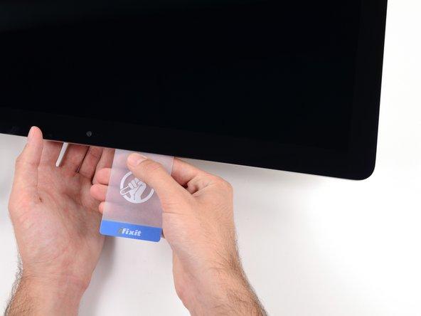 Schiebe die Plastikkarte in Richtung Mitte und höre wieder vor der  iSight Kamera auf.