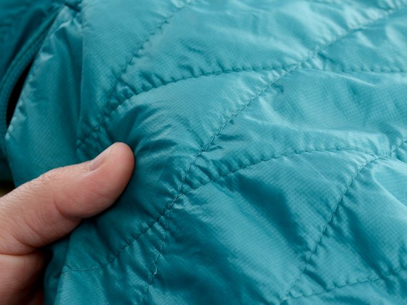 The loose thread should get caught between the lining and the outer layer of the jacket, and should not be visible on either side of the jacket.