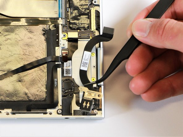 Use the needle-nose tweezers to remove the charging port by lifting the component up and out of the Pixelbook.