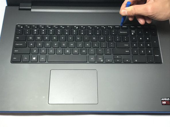 Use a plastic opening tool to gently release the tabs that secure the keyboard to the laptop.