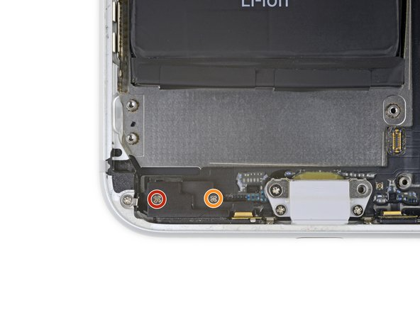 Remove the two Phillips screws securing the barometric vent at the bottom left corner of the iPhone: