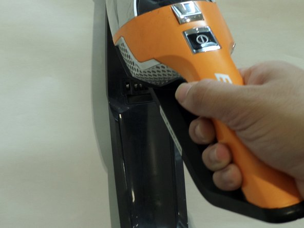 Grab handle and pull to remove vacuum from charging base.