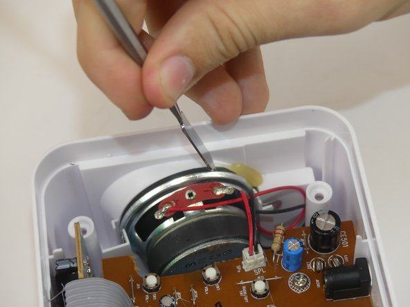 Using a black nylon spudger to carefully break the glue around the outside of the speaker so it can be dislodged.