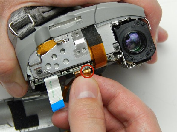 Image 3/3: Gently remove the two ribbons that are keeping the other half linked to the camera.