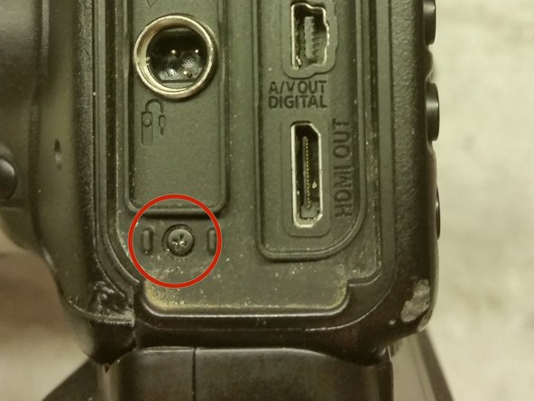 Image 1/1: Open the port covers to gain access to the screw, and remove it.