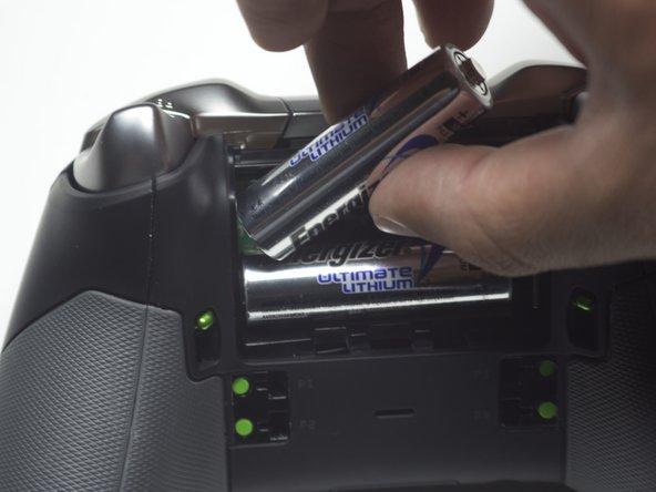 Hebe die beiden AA Akkus/Batterien an einem Ende hoch und ziehe sie heraus.