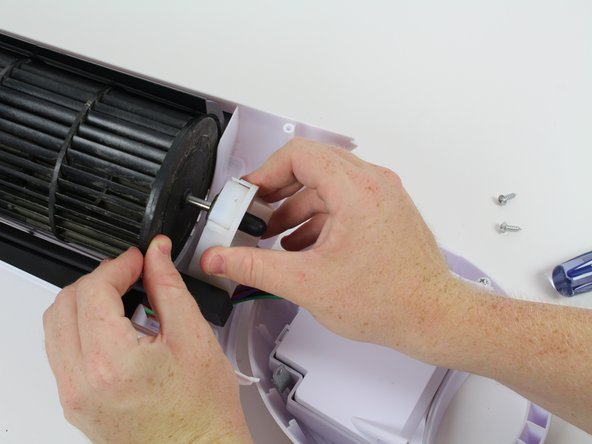 Slide the plastic fan cap off the fan while holding the fan blade to ensure it comes off smoothly.