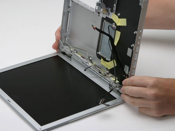 Grasp the lower case and push down on the hinge side while rotating the other end of the case toward you until it pops free, then remove it entirely (leaving the display).