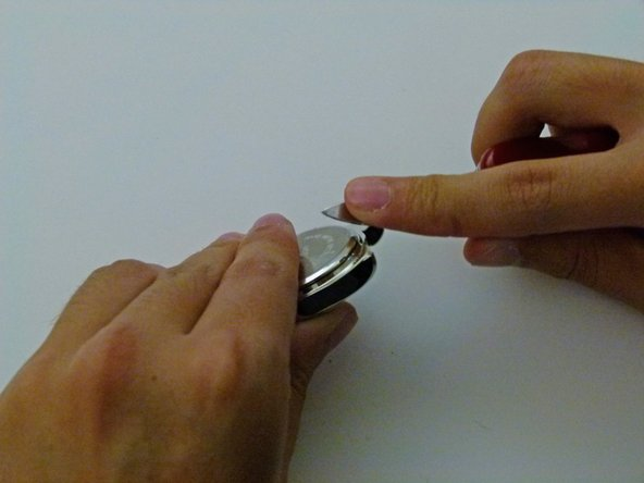 Carefully place your thin blade in the divot and pop the buckle off of your watch.