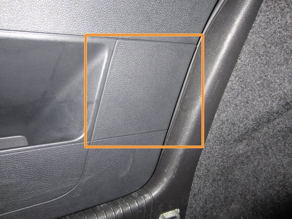 On the driver's side of the vehicle's rear cargo area, locate the rectangular tail light compartment cover.