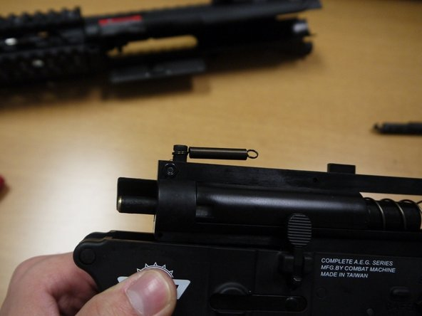 Hook the larger end of the charging handle spring on the nub on top of the bolt assembly.