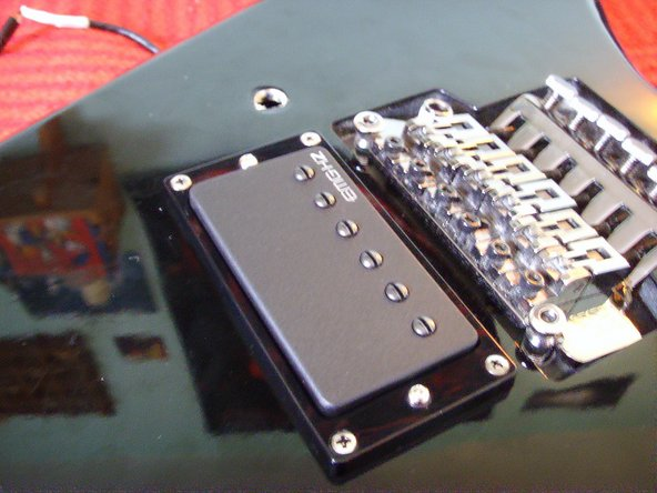 "In fact, it's a bit tricky because the hole is nearly too small for the three cables. Start with the humbuckercable and insert the outputcable instantaneous after it. Insert the ""green"" cable from the output last."