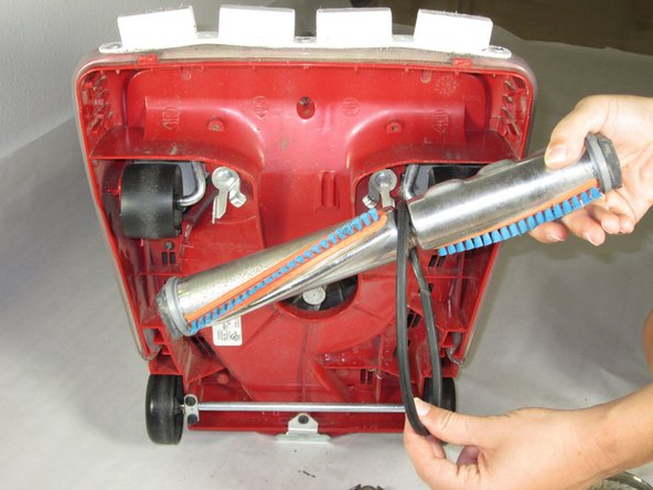 Pull brush roller out and detach the belt off the brush roller.