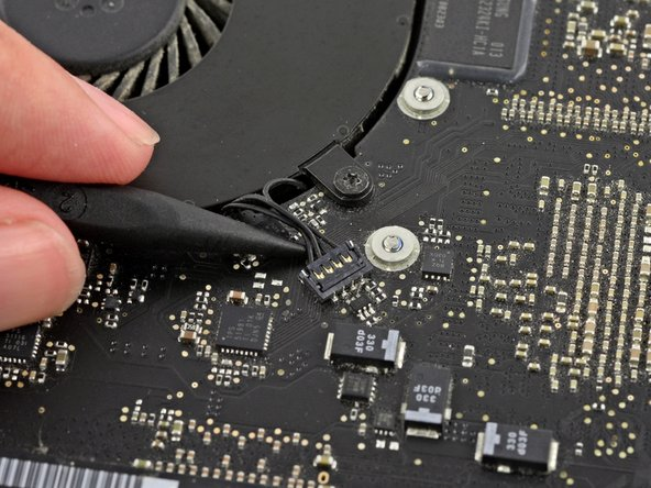 Use the tip of a spudger to lift the right fan connector straight up from its socket on the logic board.