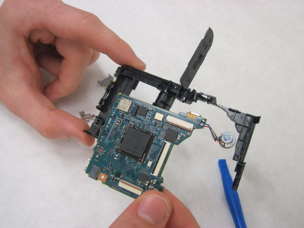 On the backside of the motherboard, a silver clip is holding the motherboard to the plastic shell. Insert the plastic opening tool under the clip and pry gently until it releases.