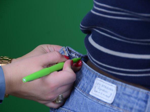 Tieni con una mano la parte in eccesso dei jeans e segna con un pennarello il punto che va a toccare la vita.