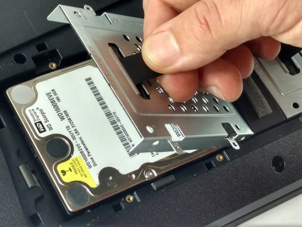 Image 2/2: Use the pull-tab to lift the hard drive housing and pull the hard drive away from the connector.