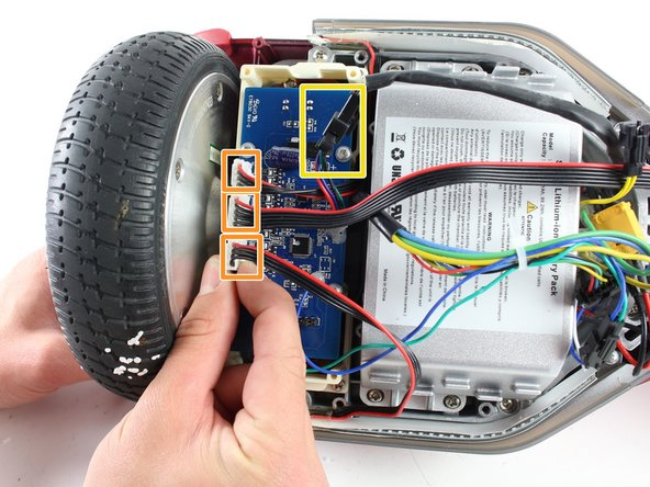 The gyroscope is a blue rectangular circuit board on top of a white base and is closest to the wheel.