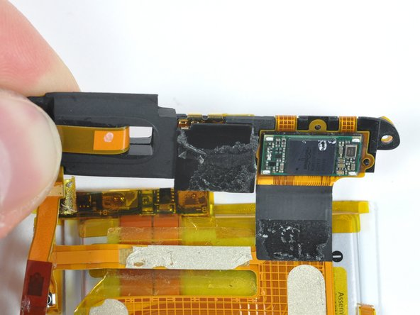 It appears that Apple left in room for a camera in the top of the device. There is a 6mm x 6mm x 3mm space between the Broadcom chip and the wireless antenna. There isn't enough depth for an iPhone-style autofocus still camera, but just enough room for the camera that Apple used in the 5th generation iPod nano.
