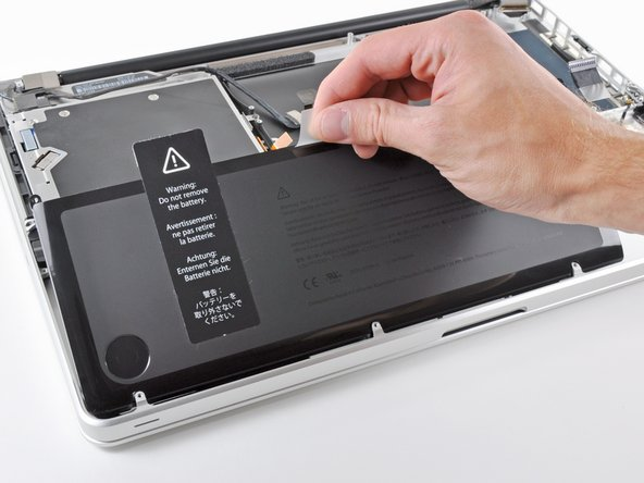 Using its attached pull tab, lift the battery out of the upper case.