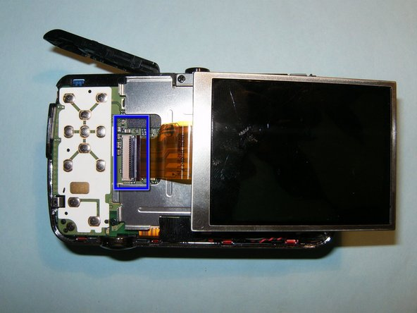 Pull the LCD screen out of its holder. Once you have access to the connecting strip, flip the clip upwards releasing the screen completely and remove.