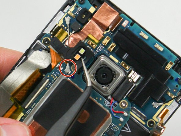 Remove the dual LED flash cover. This is held on with a small amount of adhesive. Be careful here: the flash cover may be glued to the antenna cable(s) below. Apply a small amount of heat here to soften the adhesive before removal.