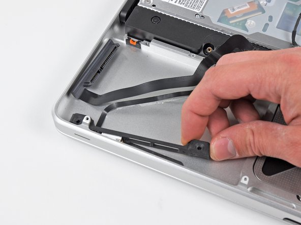 Pull the hard drive bracket/IR sensor housing away from the side of the upper case.