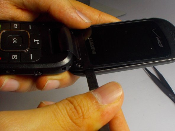Take your spudger and forcefully insert it between the black and silver part of the phone.