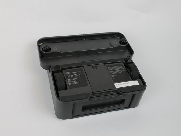 Image 1/1: The battery cover is located in the center of the device in between both wheels.