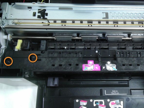 Remove the three black 9mm Torx screws and pull the black panel out from under the ink carriage.