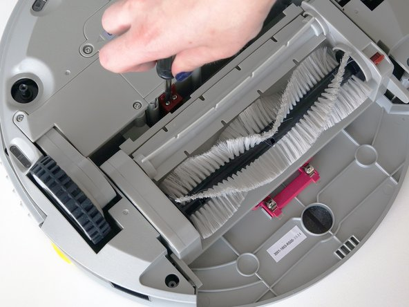 Pull the brush compartment up until it is freed from the red fastener.