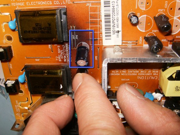 Image 1/3: Once the capacitors are inserted, bend the leads toward the logic board. This will ensure that the caps are tight to the board, it will also make it easier to solder them.